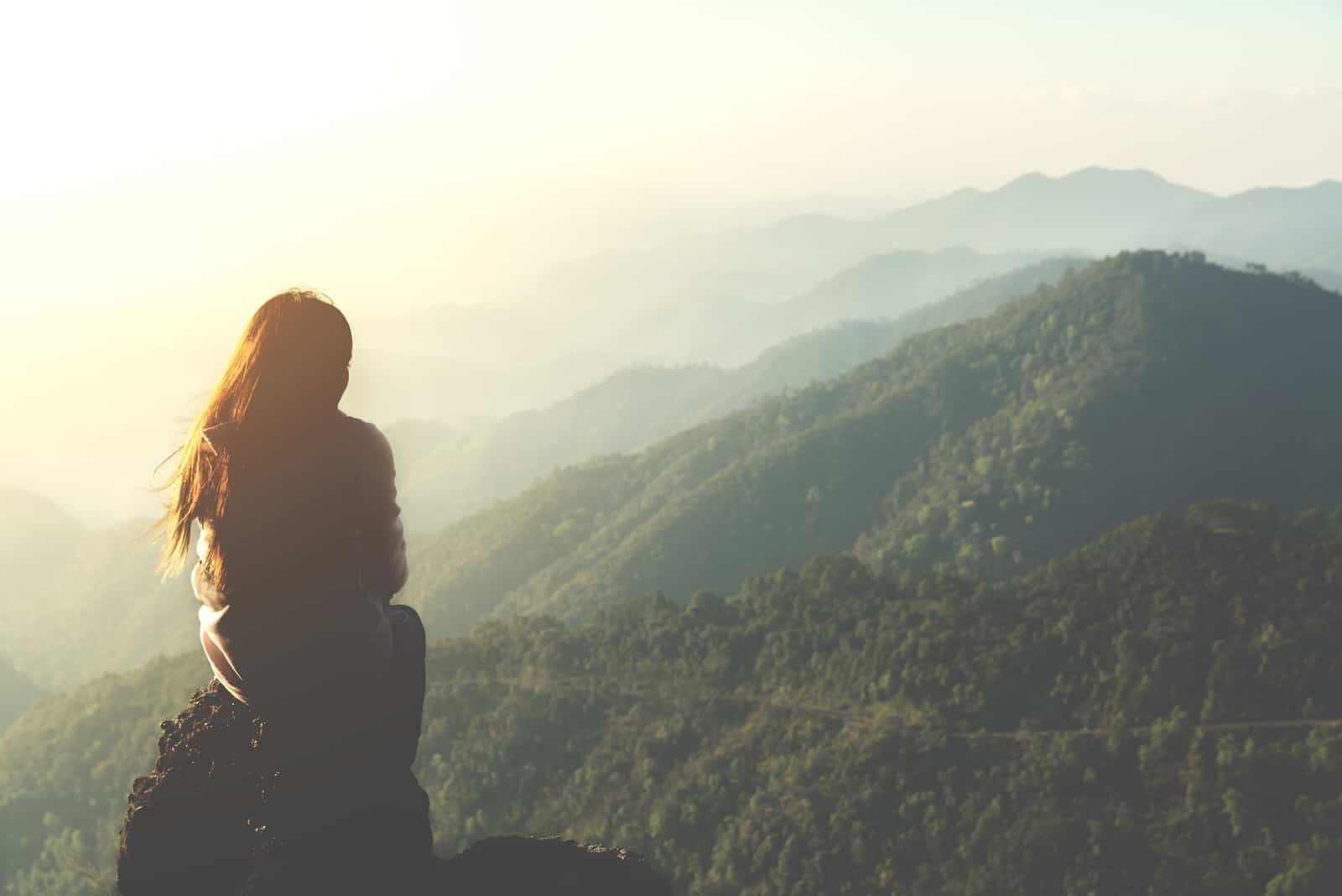 une femme assise sur une pierre