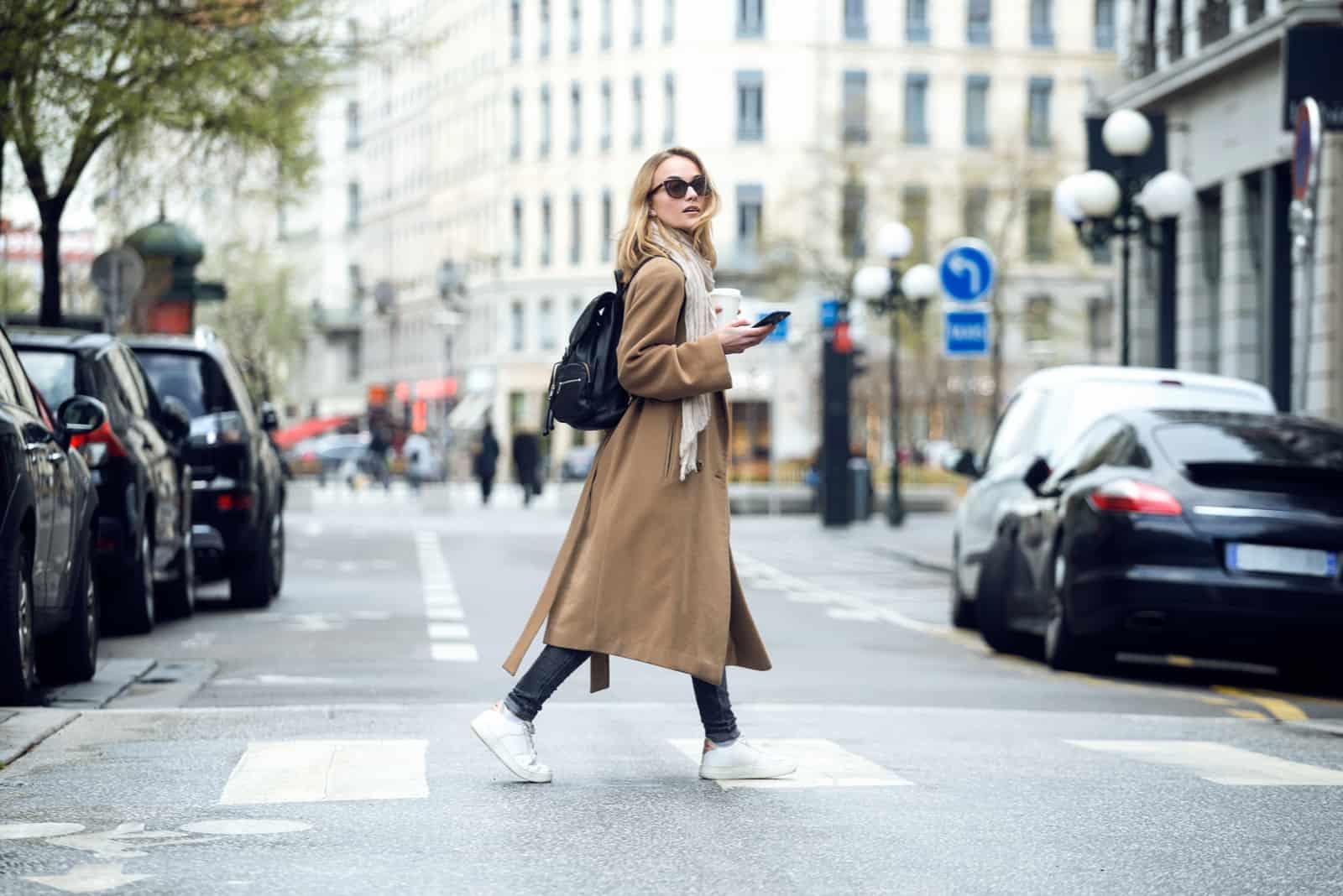 une femme aux cheveux blonds marche dans la rue