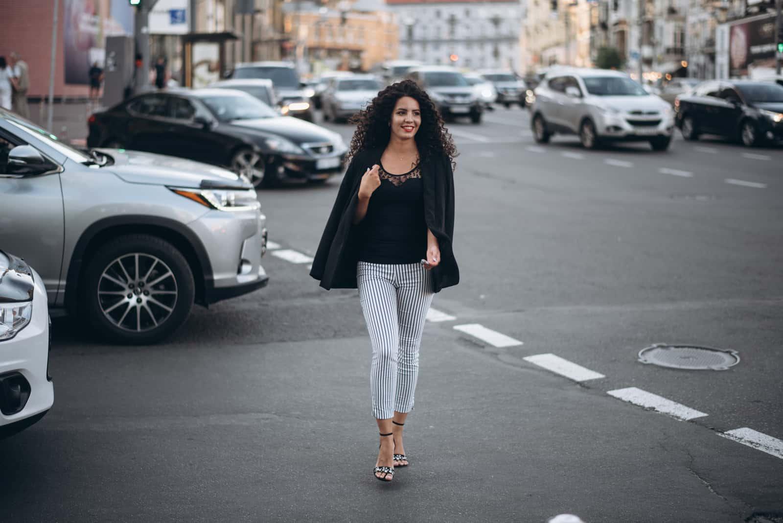 une femme aux cheveux crépus marche dans la rue