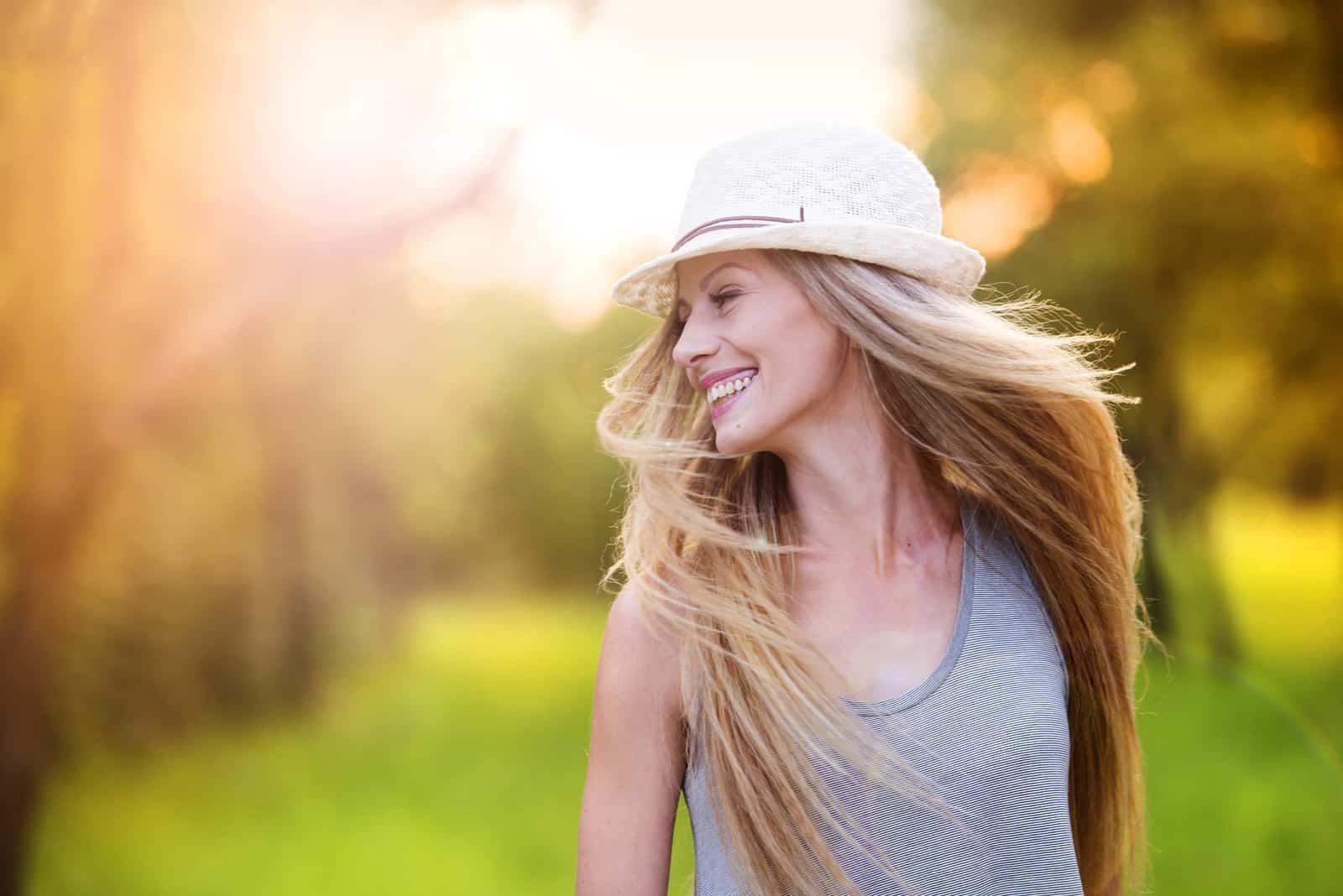 une femme aux longs cheveux blonds avec un chapeau rit