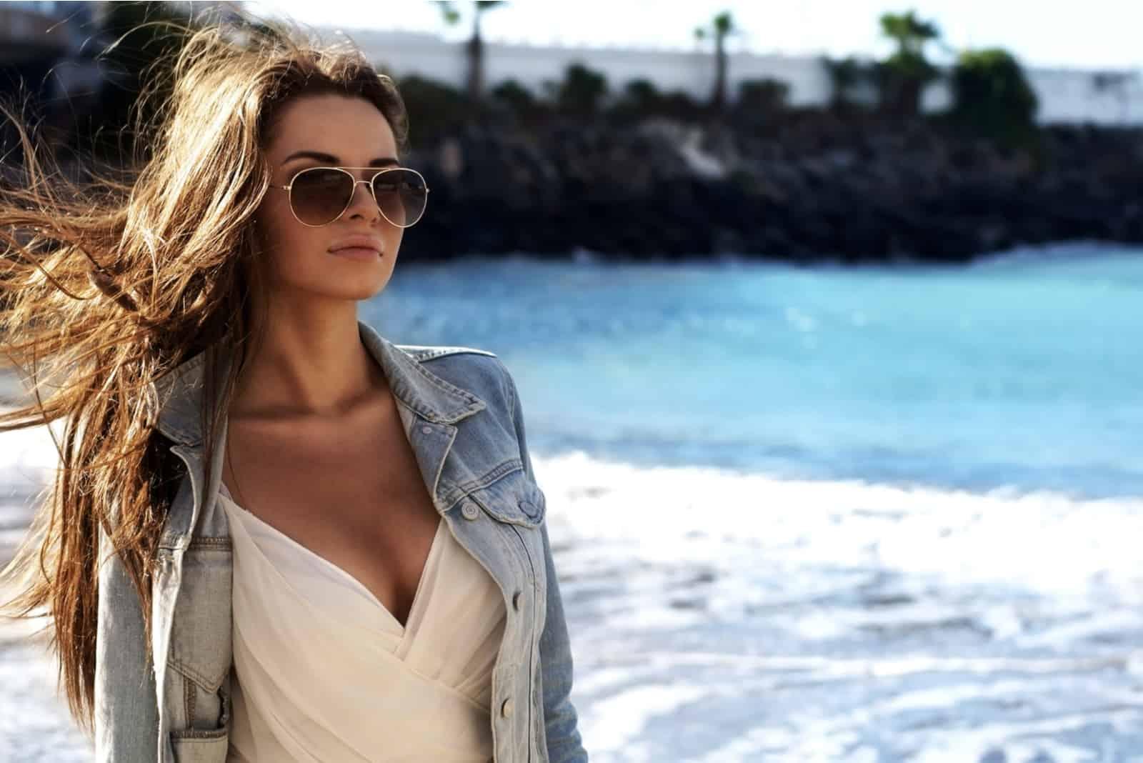 une femme aux longs cheveux bruns et lunettes se dresse au bord de la mer