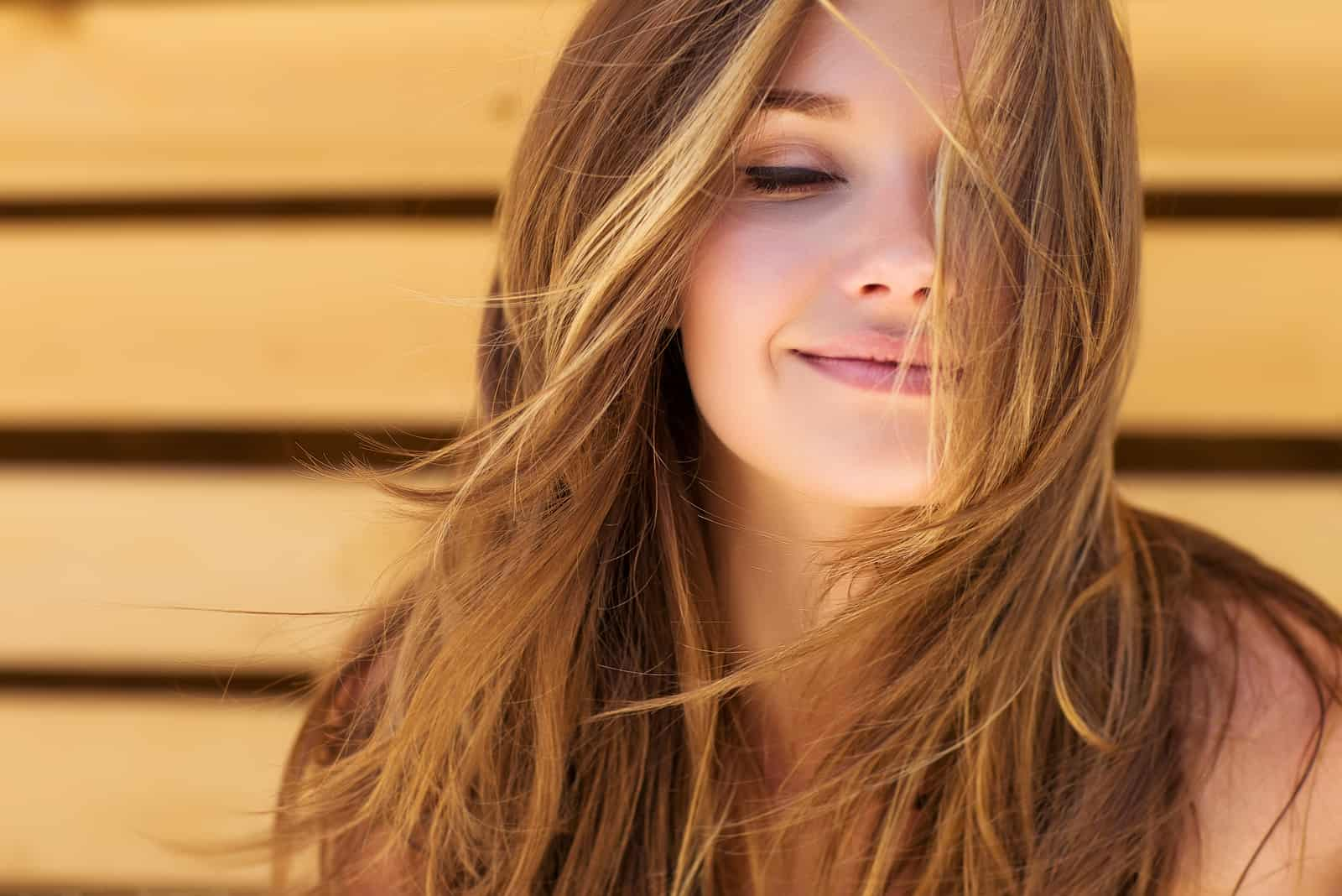 une femme aux longs cheveux bruns, les yeux fermés