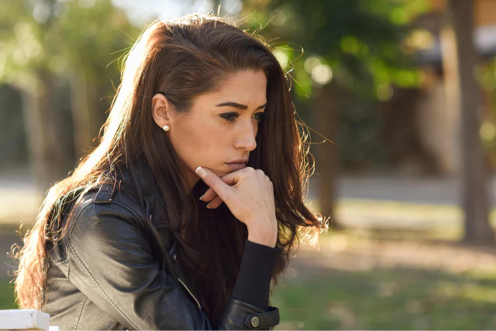 une femme aux longs cheveux noirs est assise pensif