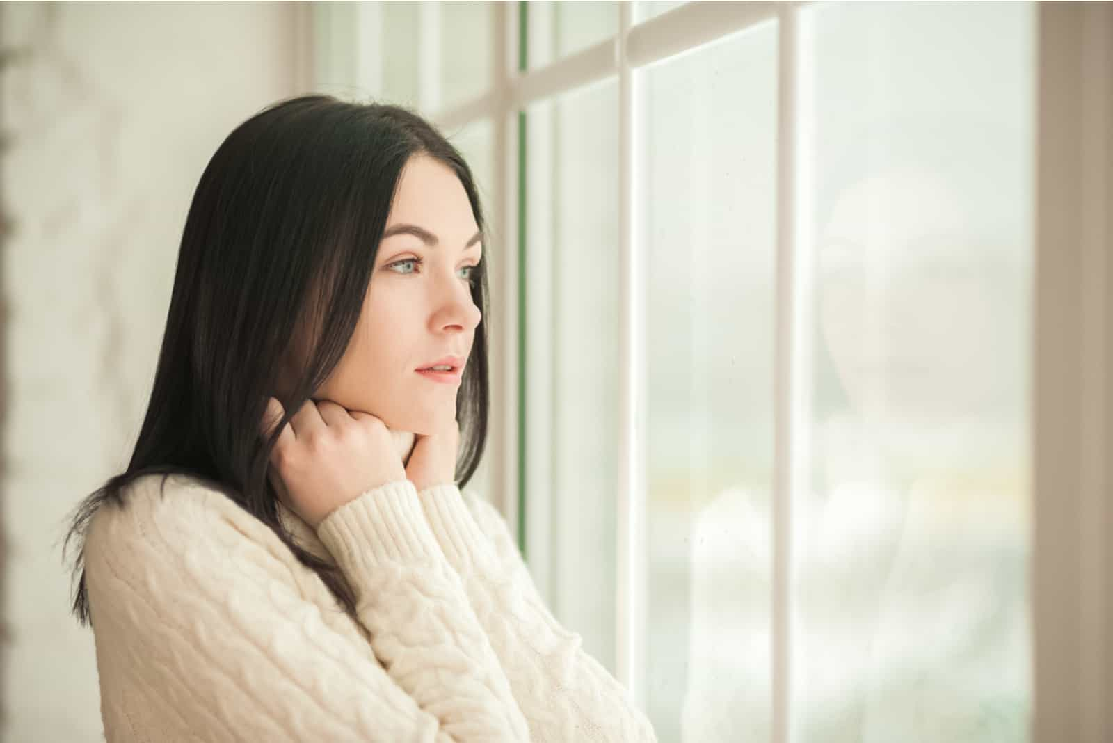 une femme déçue se tient près de la fenêtre