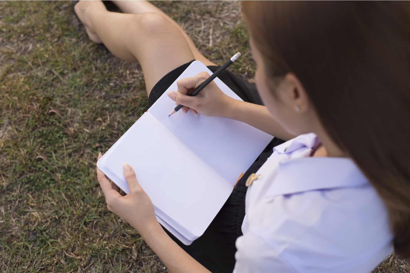 une femme est assise sur l'herbe et écrit