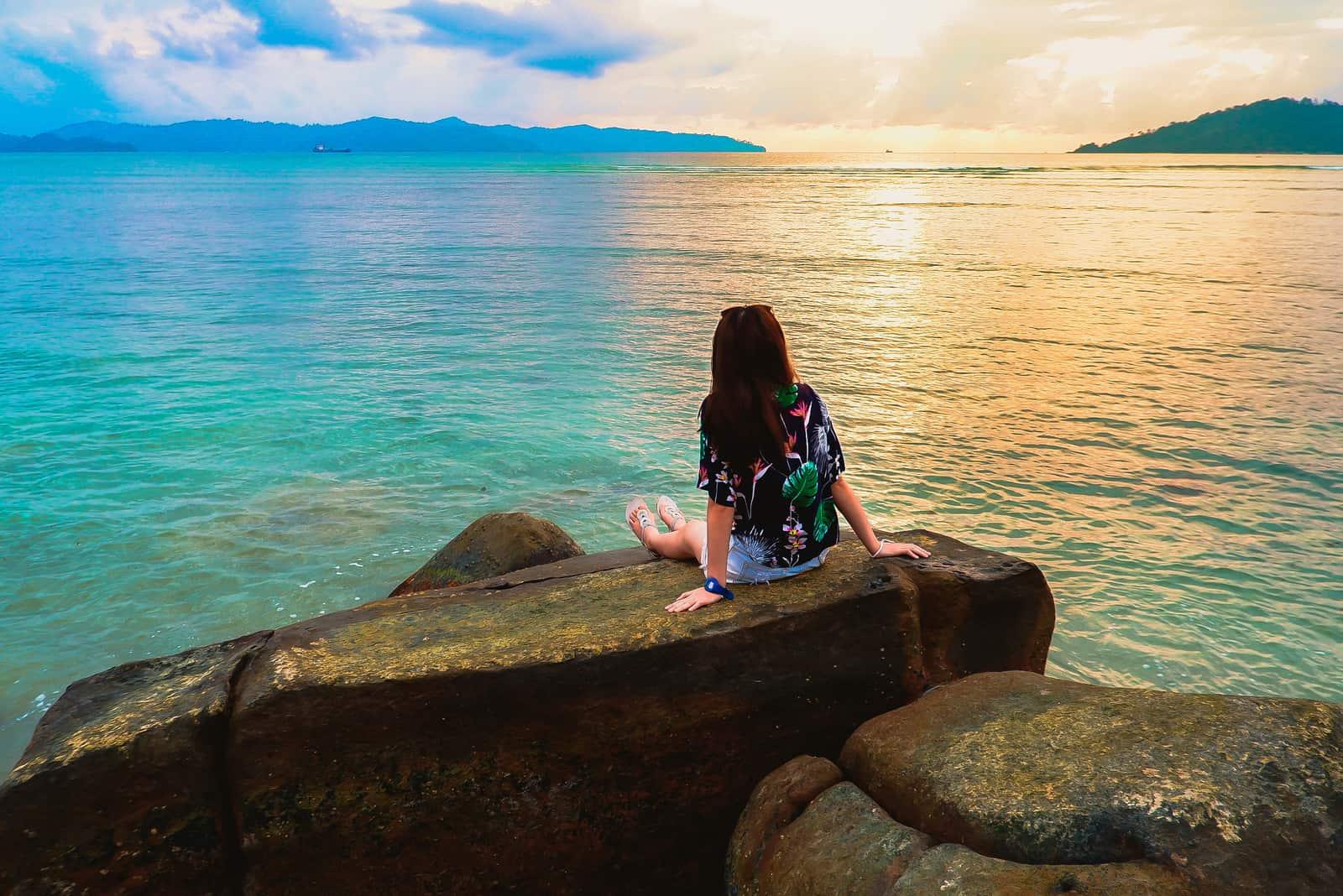 une femme est assise sur un rocher et regarde la mer