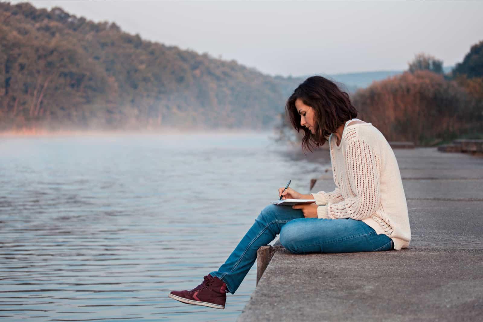 une femme est assise sur une jetée et écrit