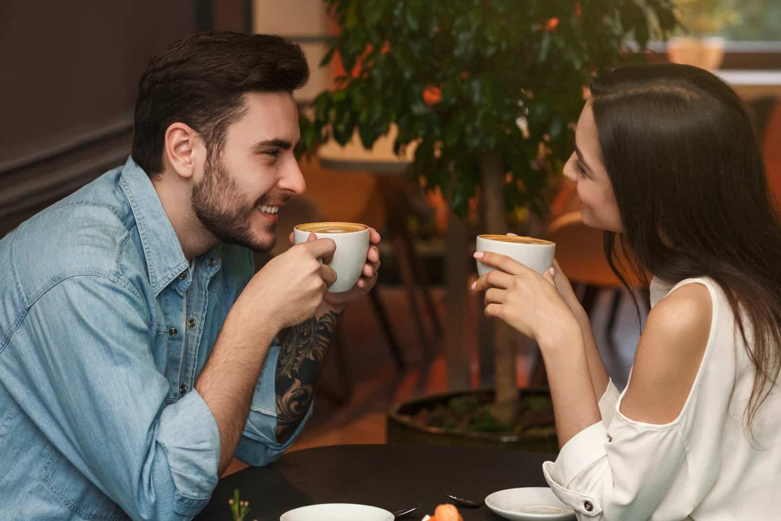 une fille et un mec dans un restaurant discutant autour d'un verre