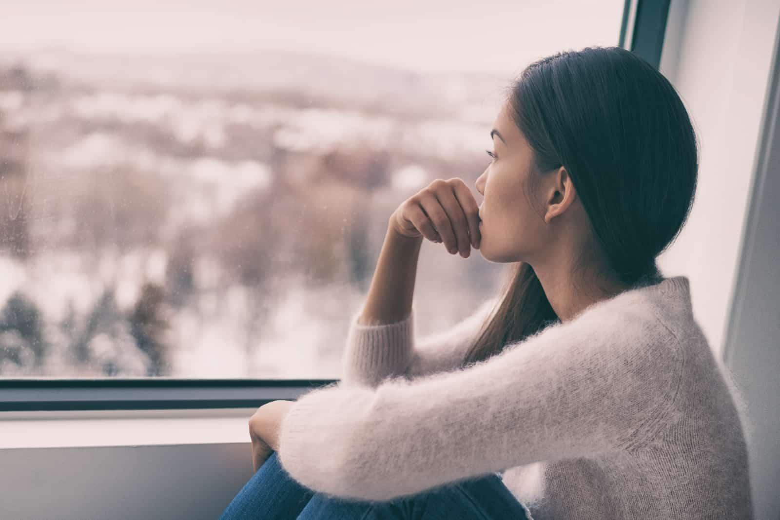 une fille inquiète regarde par la fenêtre
