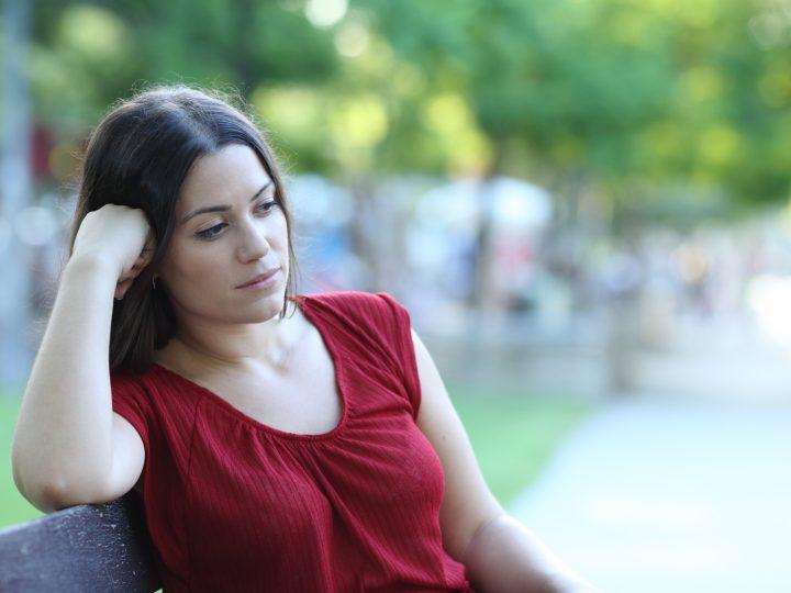 femme réfléchie assis à l'extérieur