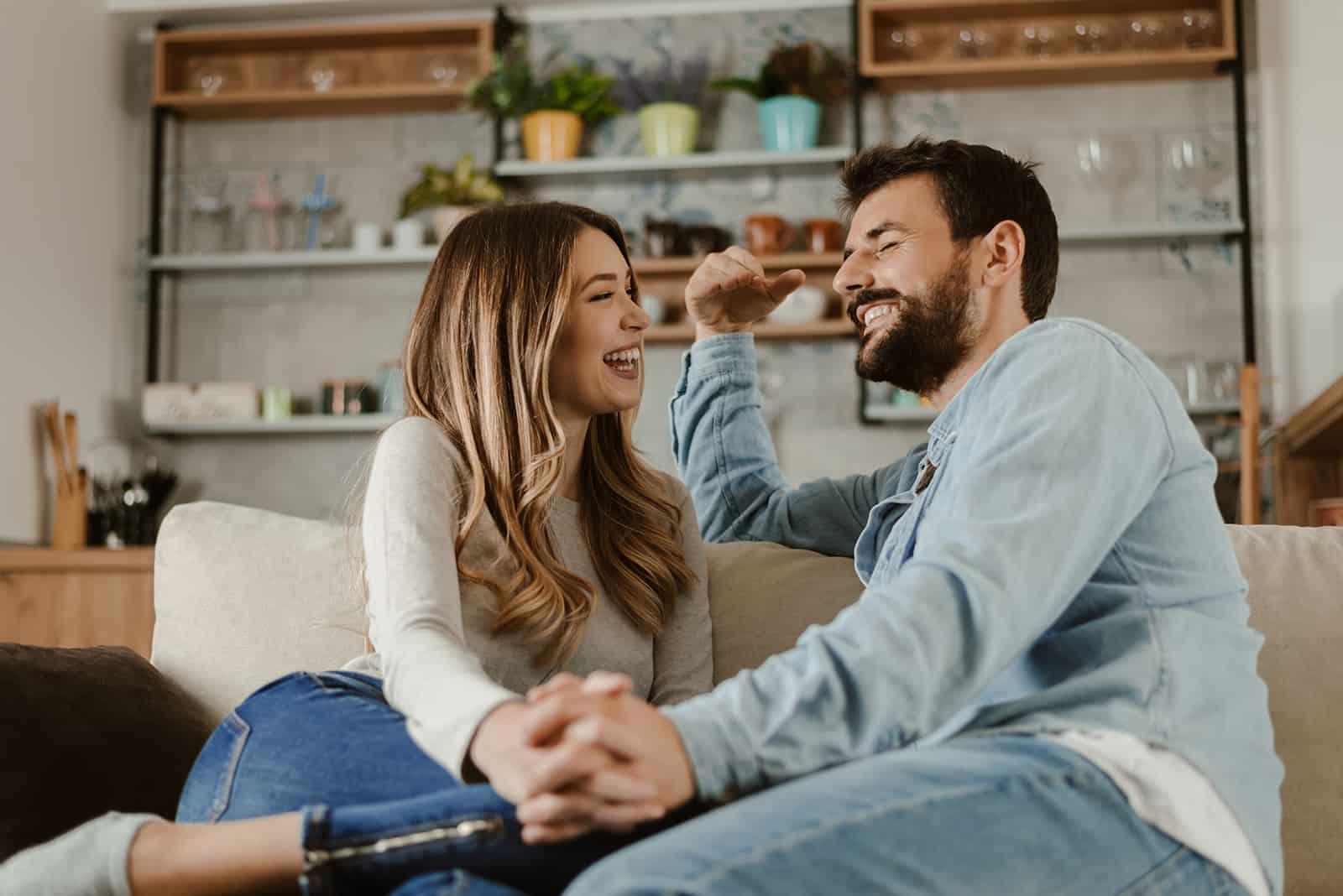Aimer heureux couple se parler à la maison assis sur le canapé et se tenant la main