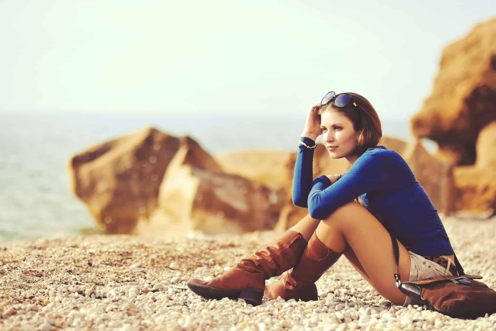 Belle jeune femme en bottes de cuir sur la rive d'une plage