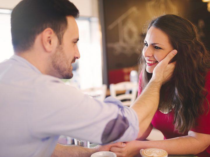 un homme touchant un visage de femme souriante dans le café