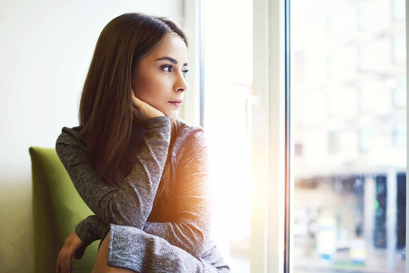 Femme attirante consciente regardant par la fenêtre