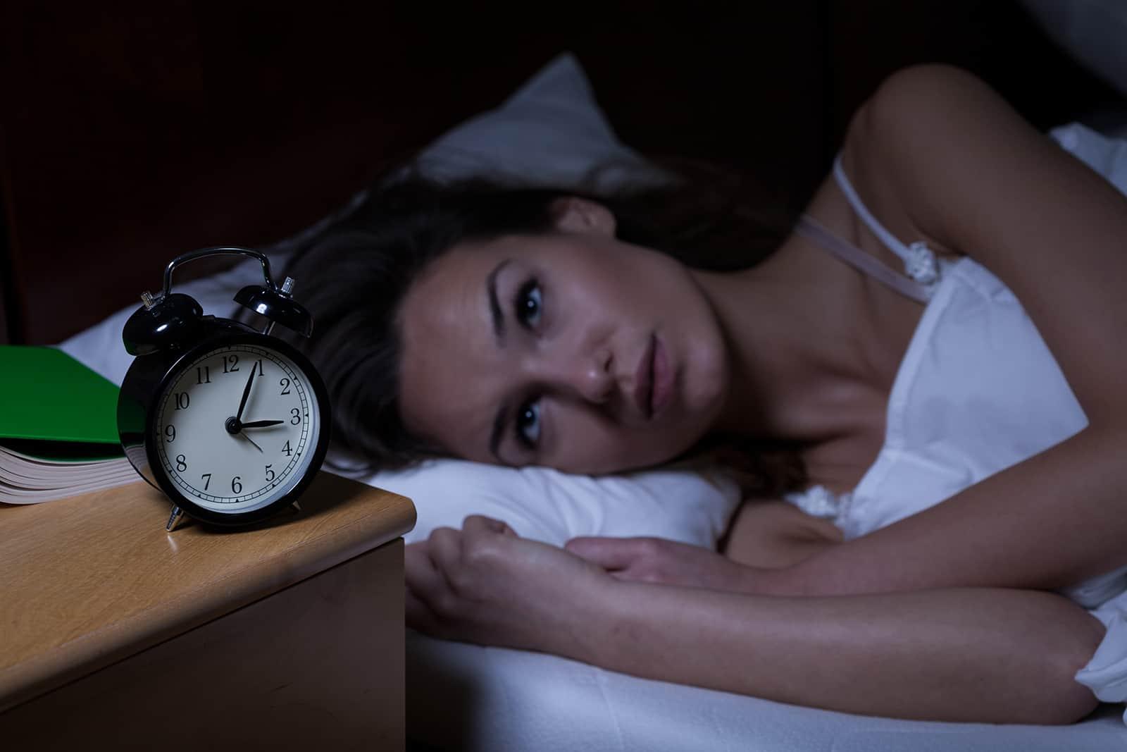 Femme avec insomnie couchée dans son lit avec les yeux ouverts