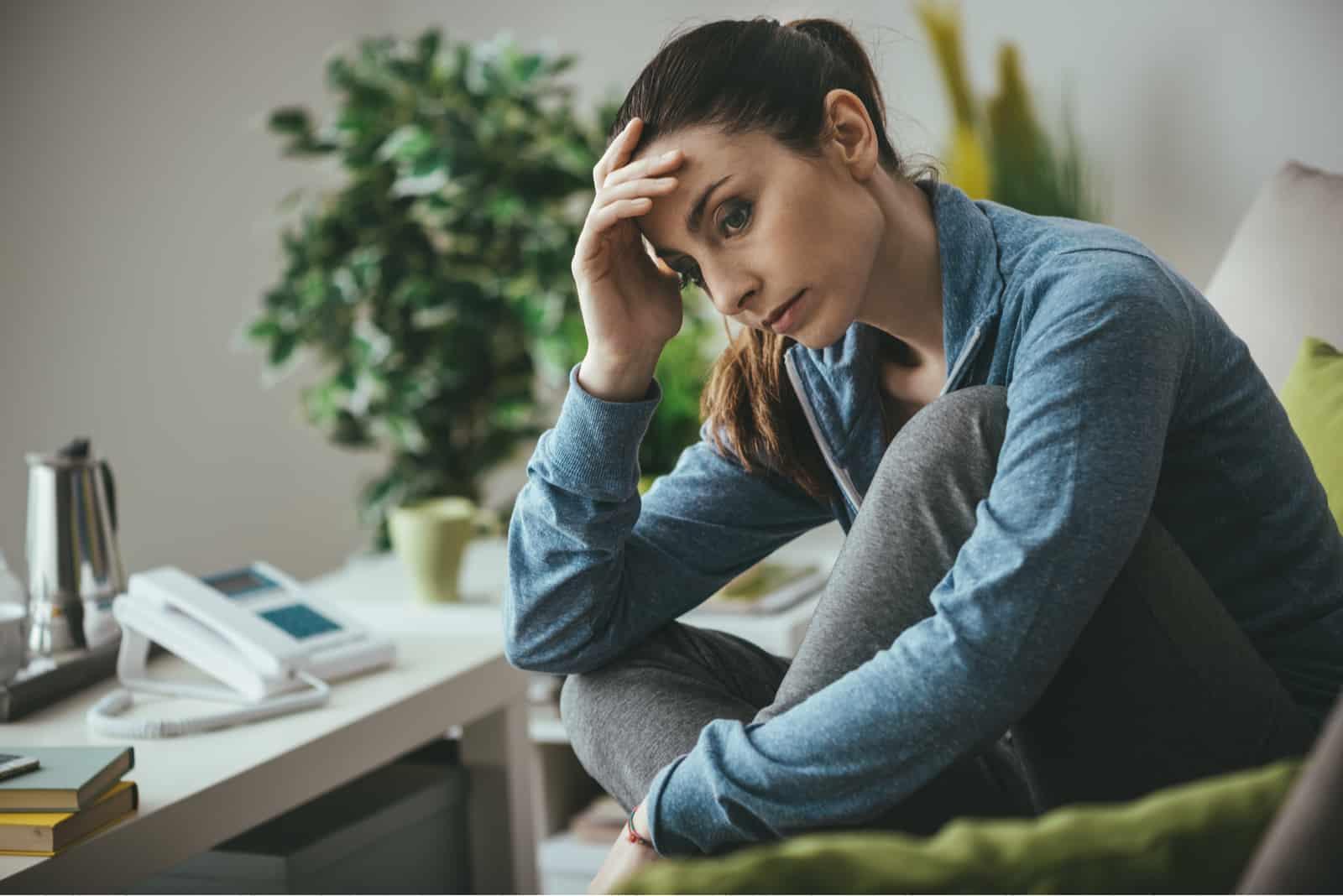 Femme déprimée triste à la maison assise sur le canapé
