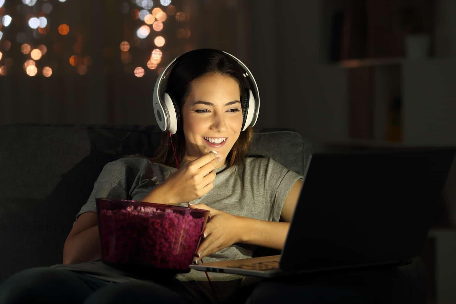 Femme regardant la télévision en ligne dans la nuit assis sur un canapé