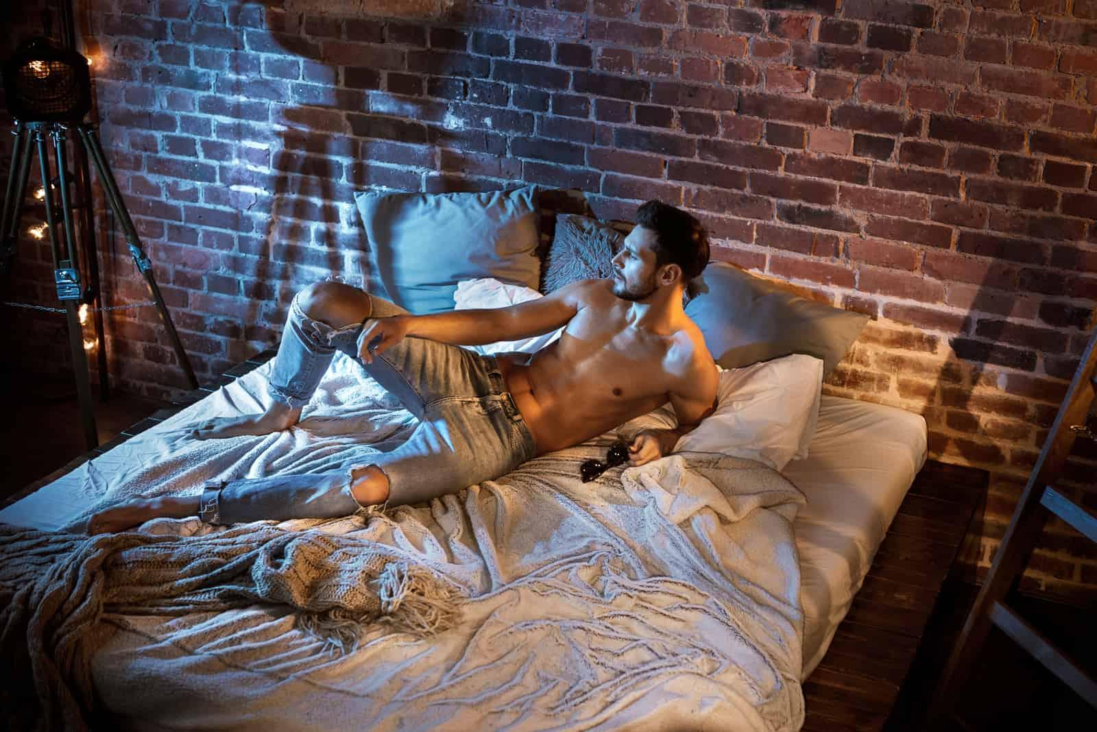 Jeune homme sexy allongé sur un lit