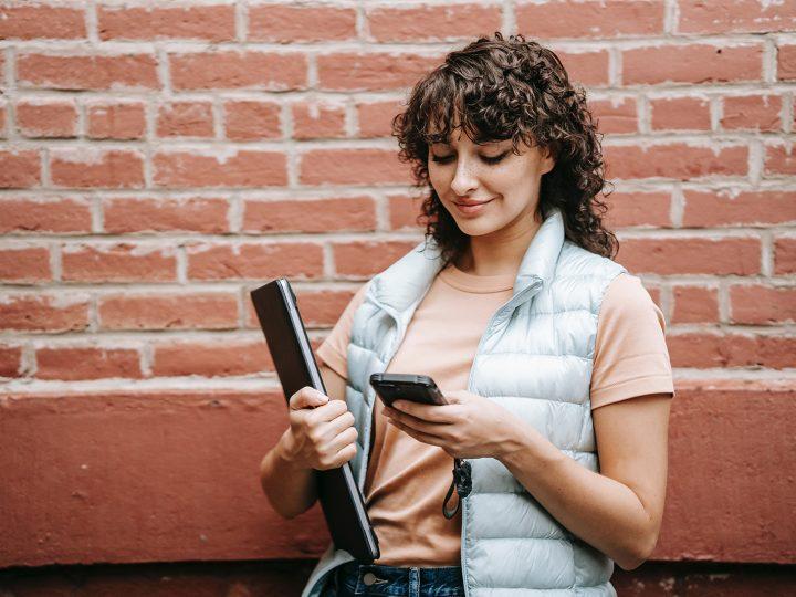 Une femme souriante lisant un message texte sur le téléphone