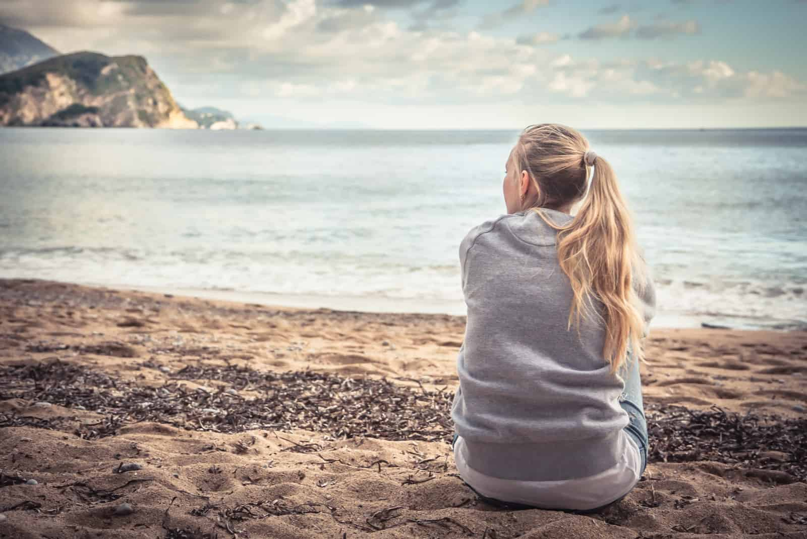 Pensive jeune femme solitaire assis sur la plage