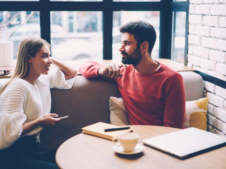 Femme et homme parlant lors de la première date dans un café confortable