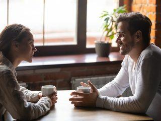 un homme souriant parle à une femme dans le café