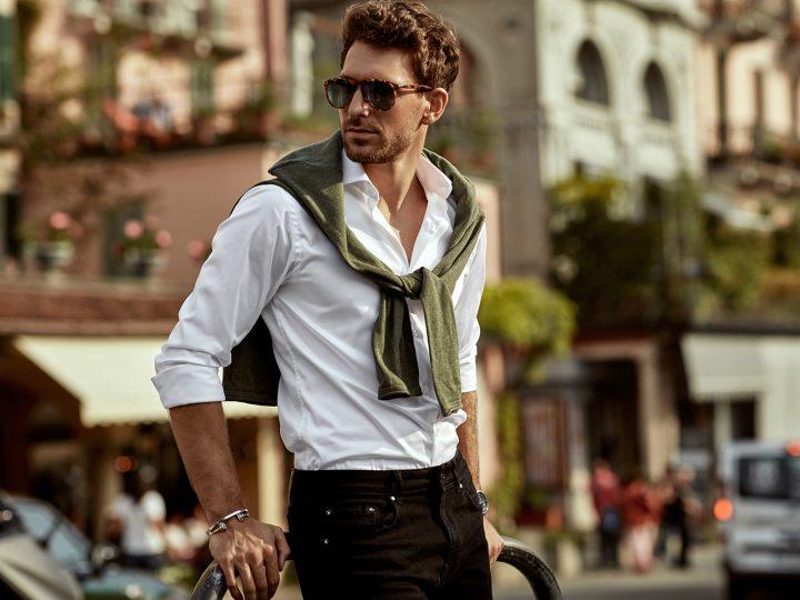 bel homme avec des lunettes de soleil s'appuyant sur la main courante