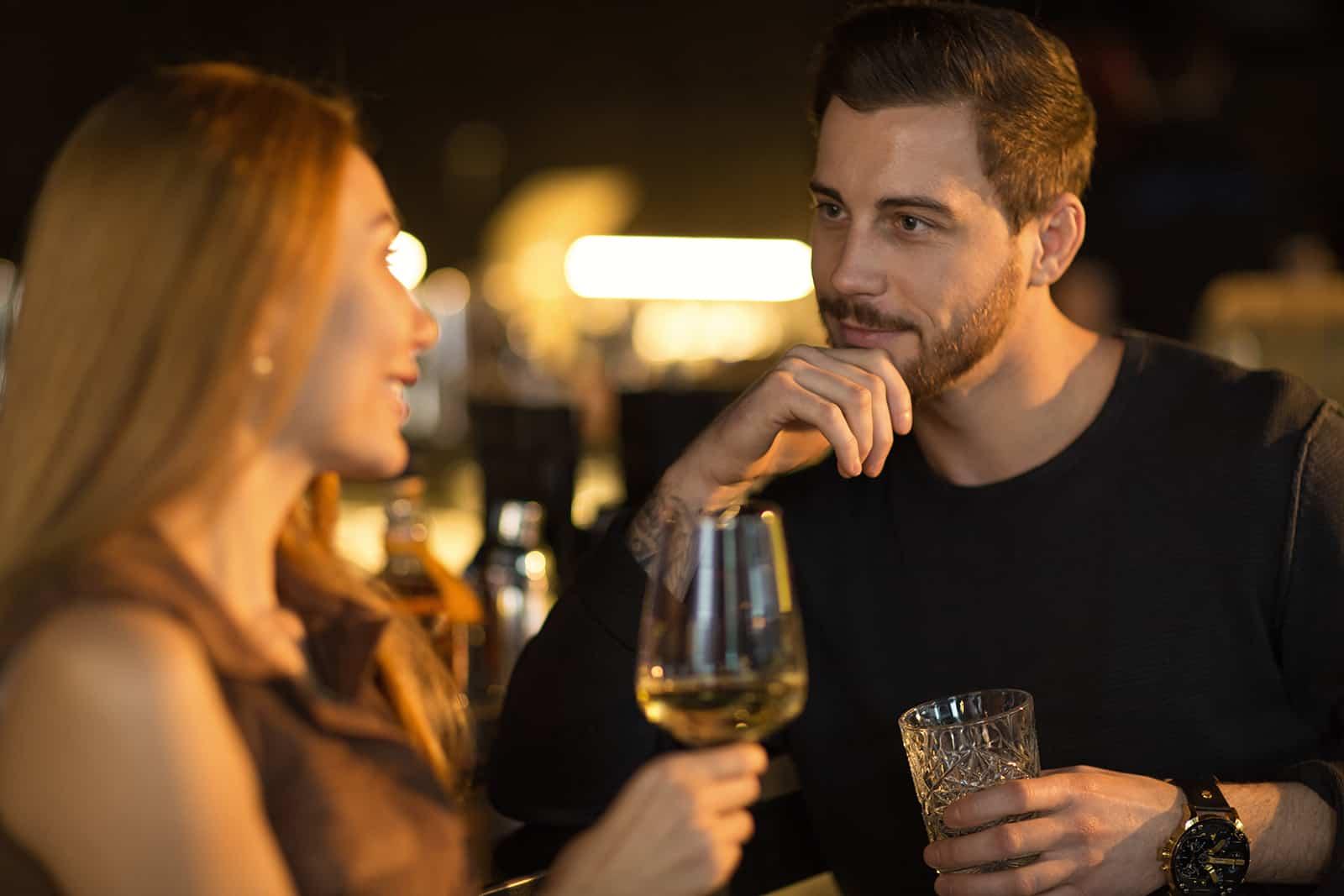 Un bel homme barbu écoutant attentivement une femme souriante tout en prenant un verre ensemble dans le bar