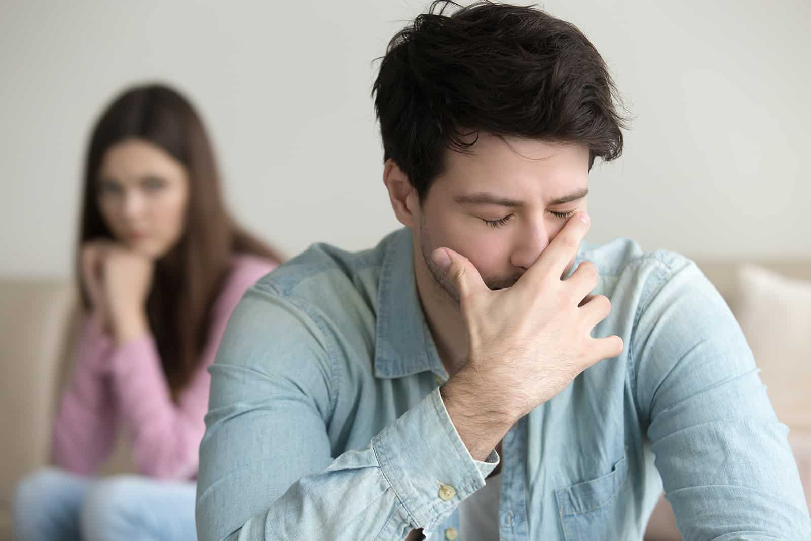 Un homme bouleversé se sentant coupable couvrant son visage avec la main assise près de sa femme