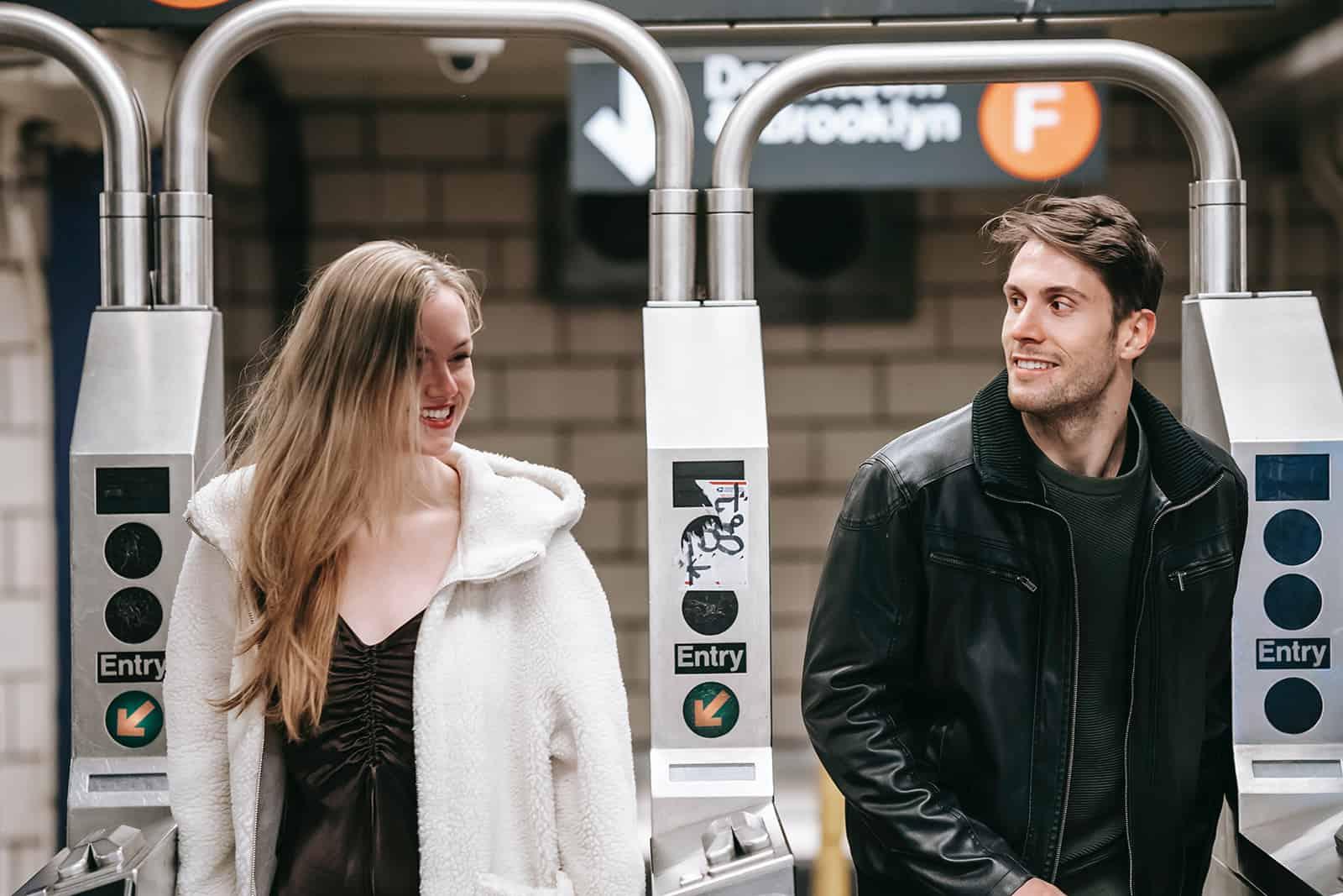 Un homme et une femme joyeux marchant à travers le tourniquet dans le métro et passer du temps ensemble