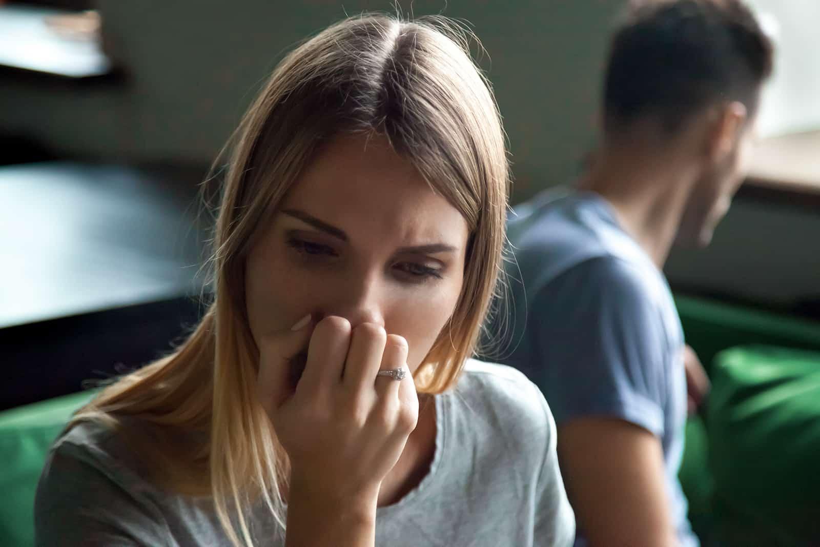 Une femme frustrée assise séparée sur le canapé avec l'homme à la maison, couvrant le visage avec la main