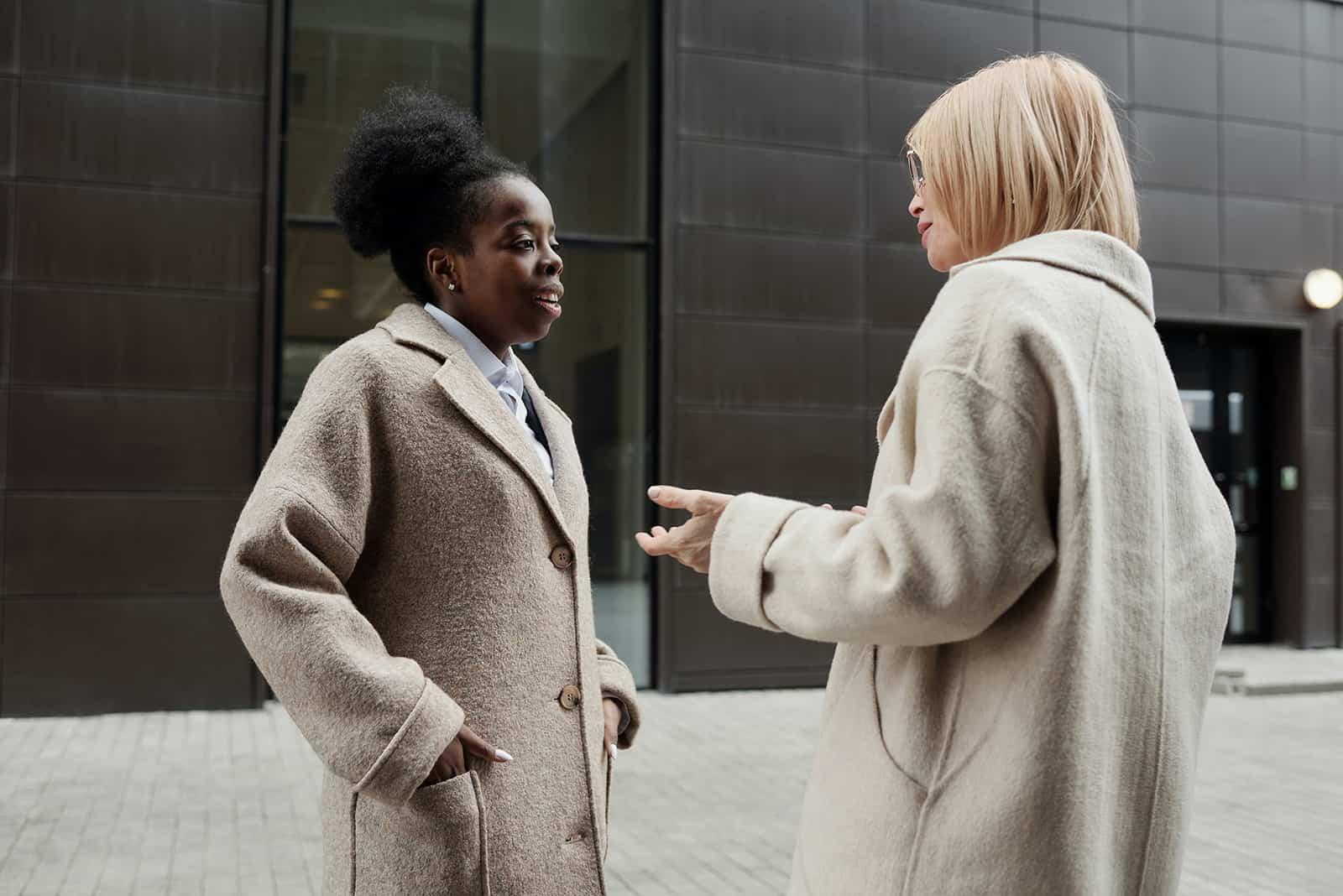 Une femme se sentant mal à l'aise de parler avec une collègue debout dans la rue