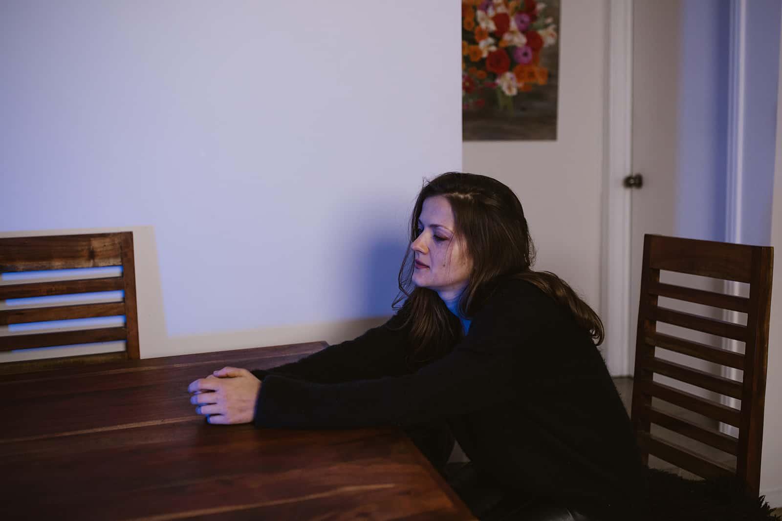 Une triste femme seule assise à la table à la maison