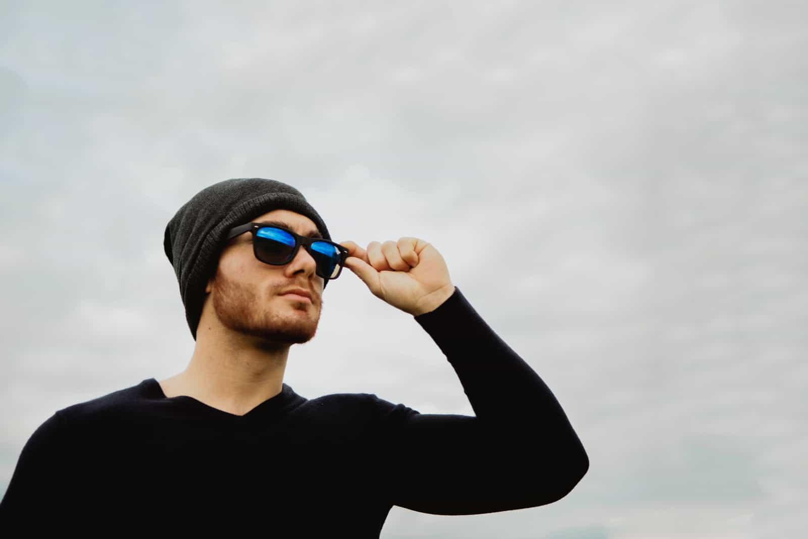 cool jeune homme à lunettes soleil et casquette
