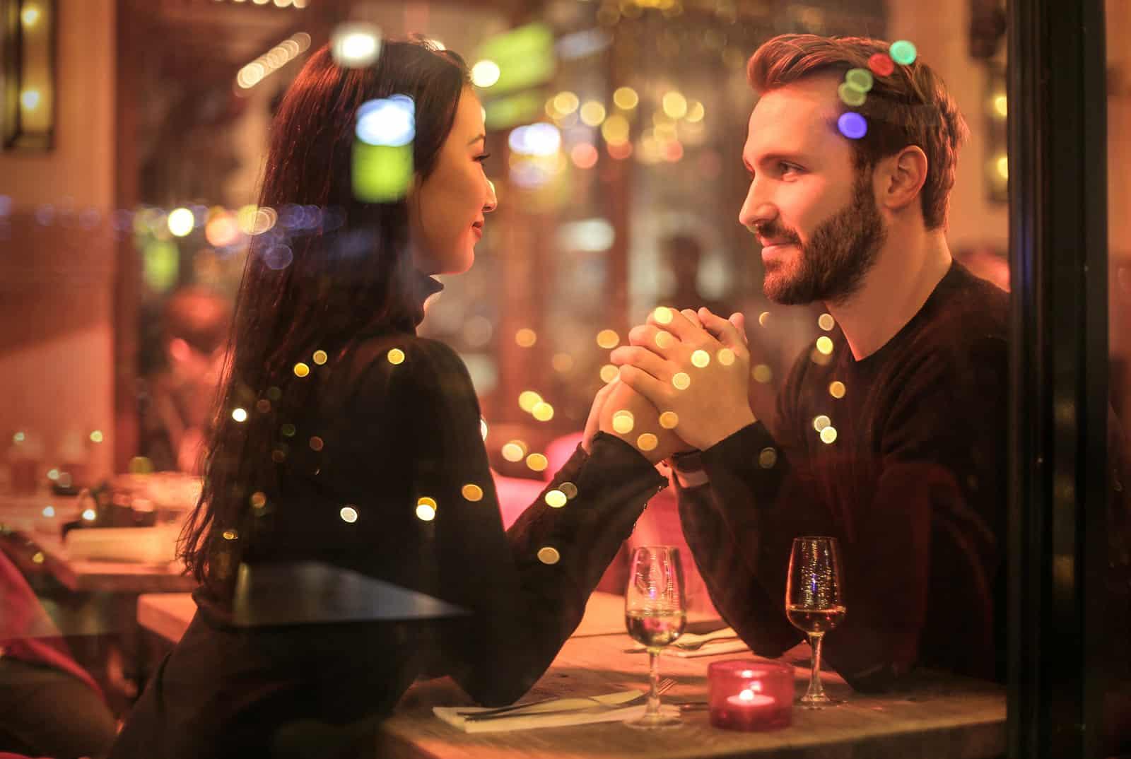 un couple main dans la main dans un restaurant et se regardant