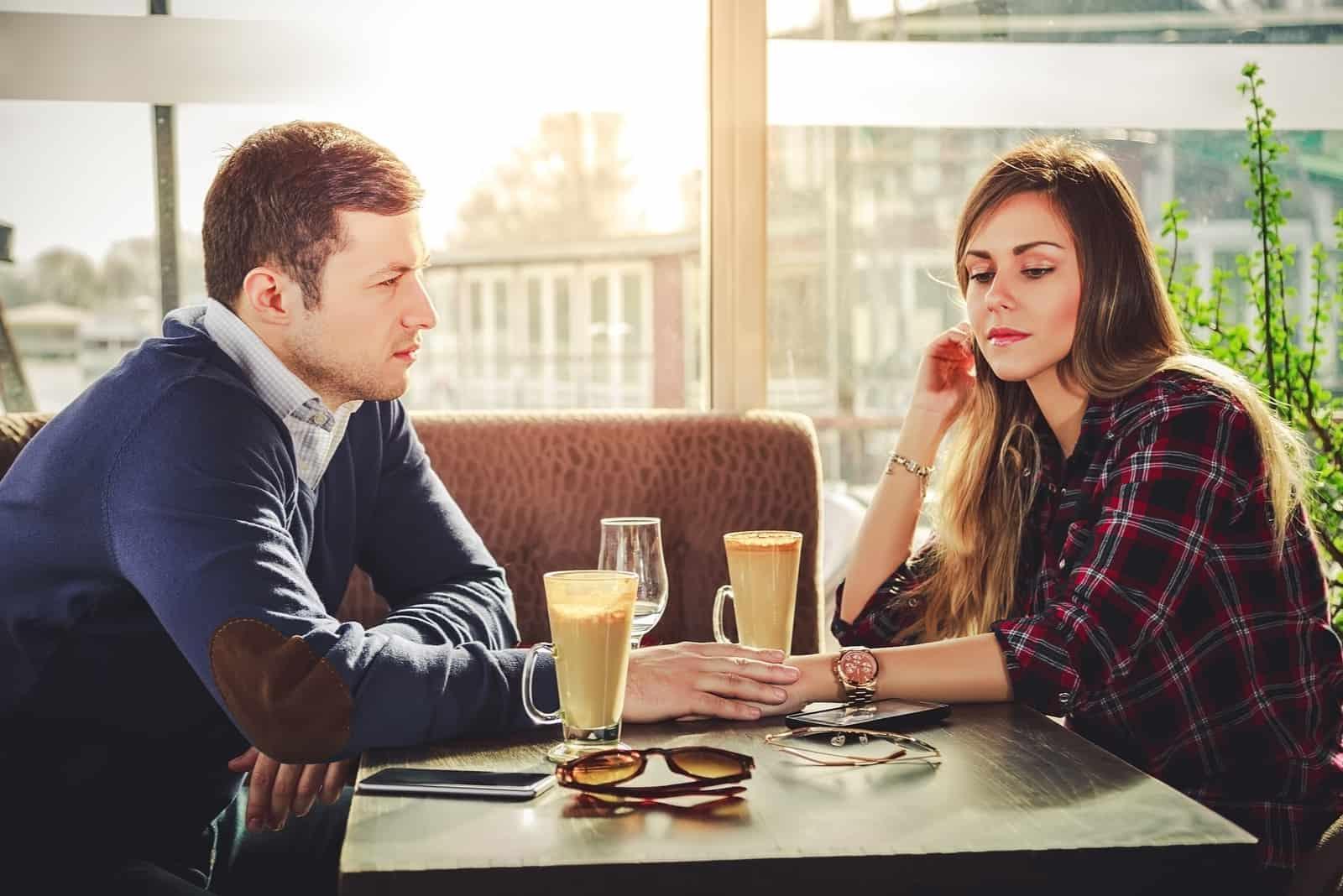 couple sérieux assis au restaurant