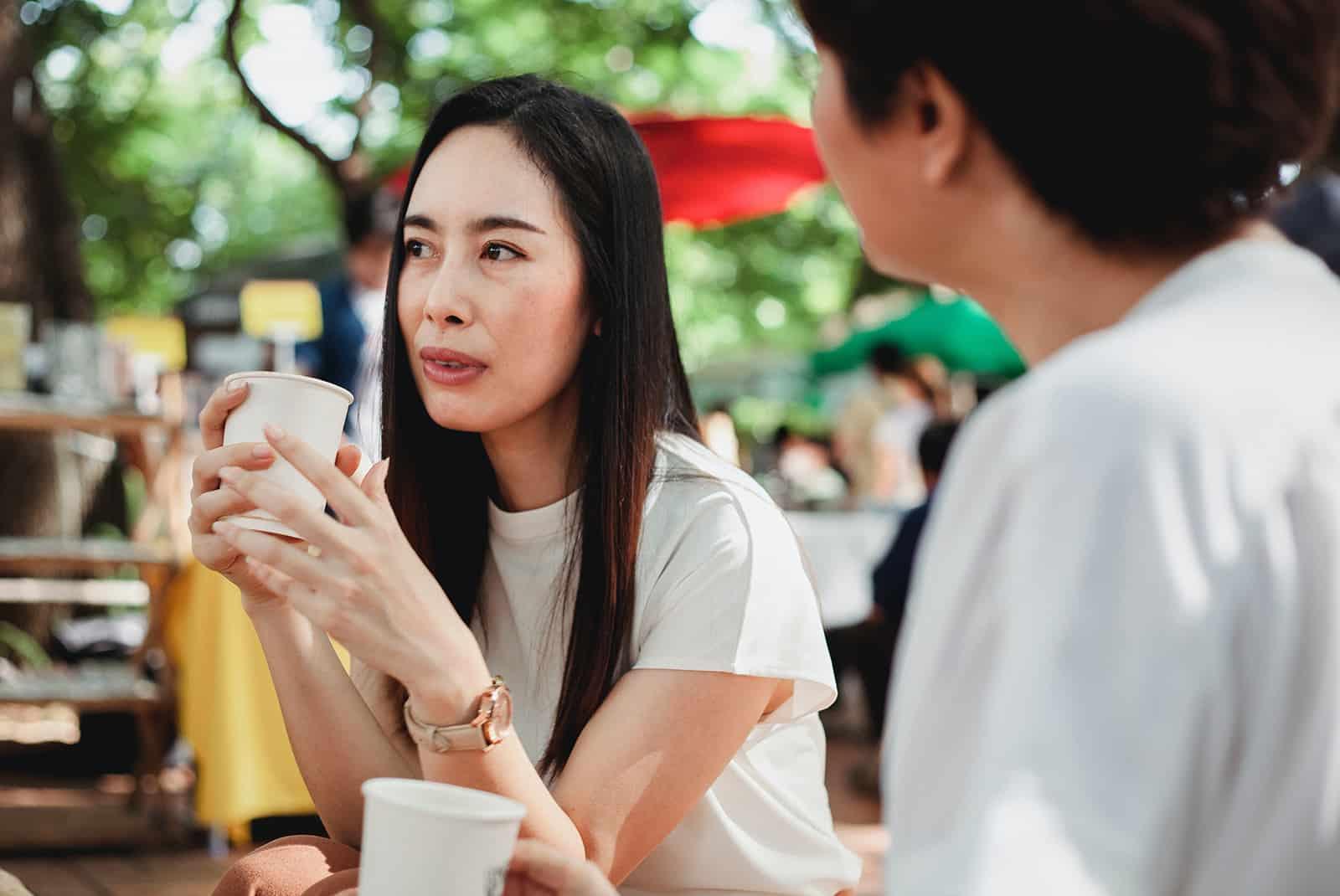 Deux amies ayant une conversation sérieuse tout en buvant du café dans la rue