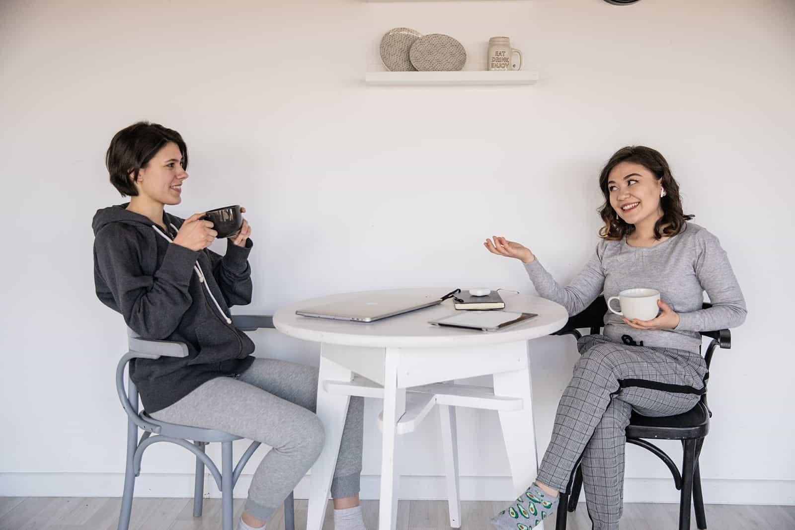Deux amies proches parler et boire du café à la maison
