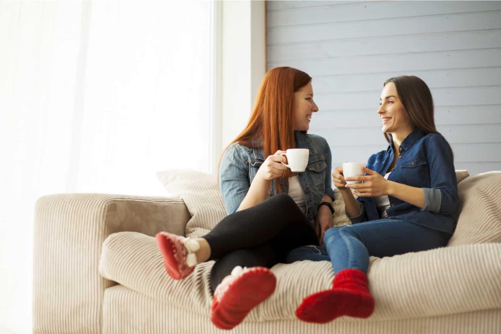 deux femmes assises sur un canapé à la maison parler