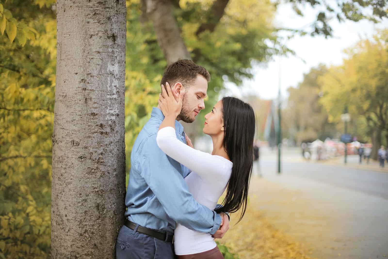 hugging couple regardant les uns les autres tout en se tenant à côté d'un arbre