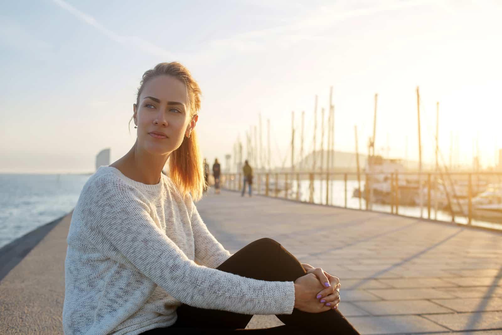 femme assise seule au bord de la mer