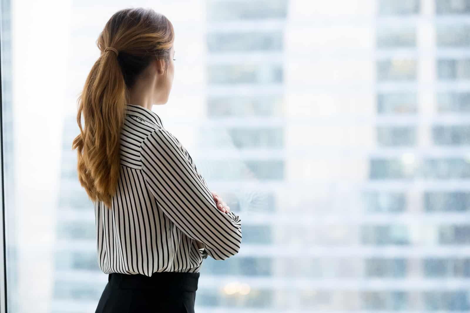 femme debout près de la fenêtre seule