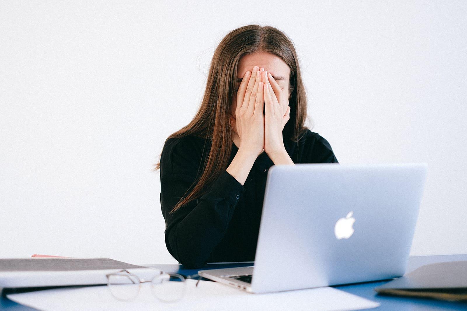 Femme en détresse couvrant le visage avec des paumes alors qu'il était assis devant un ordinateur portable