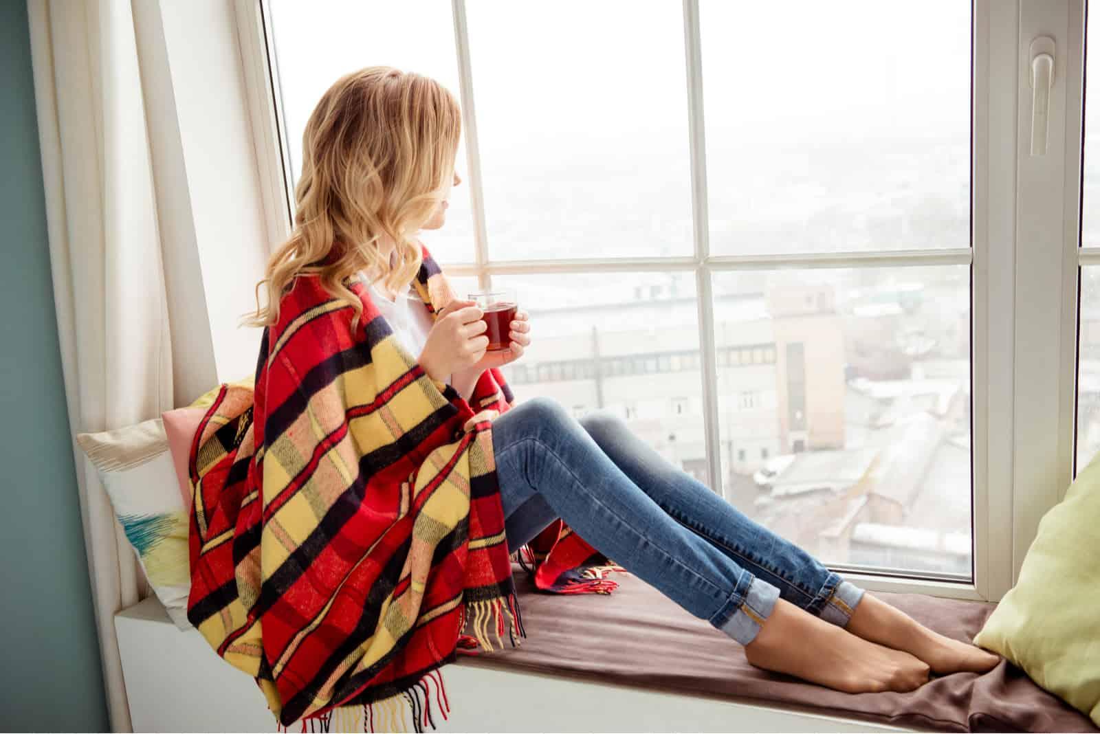 femme en plaid avec tasse de thé chaud