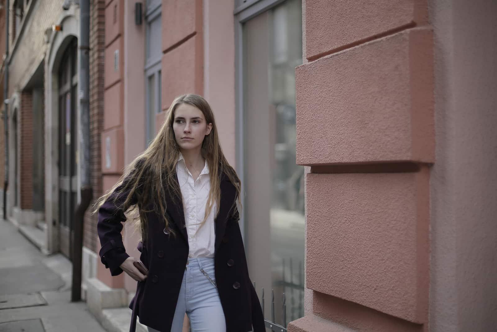 une femme qui marche sur le trottoir et regarde de côté