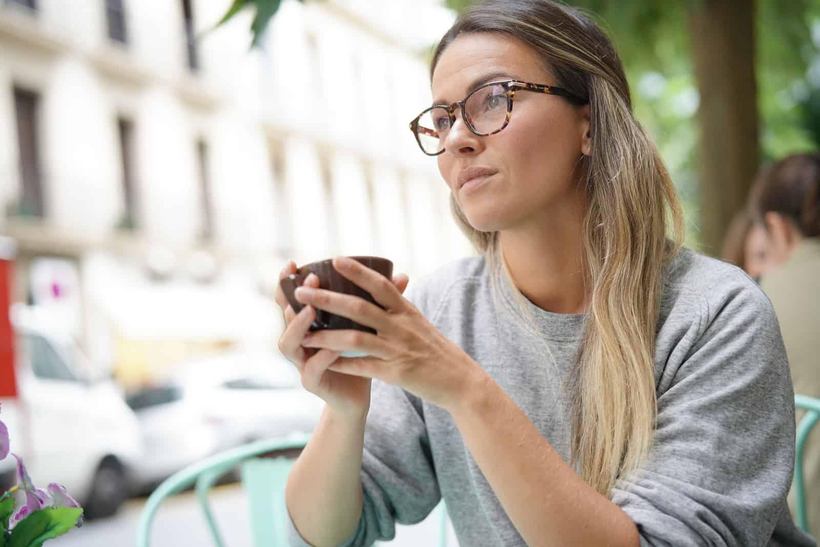 femme pensive portant des lunettes prenant un café