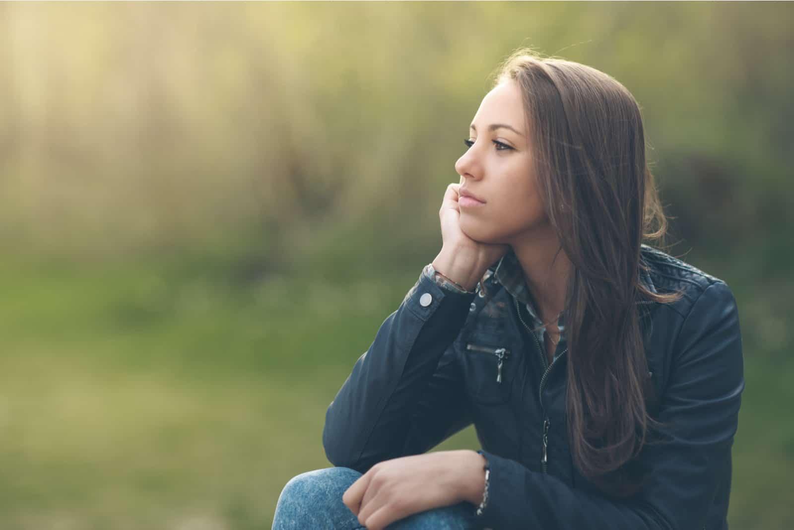 femme pensive se détendre dans le parc et assis sur l'herbe