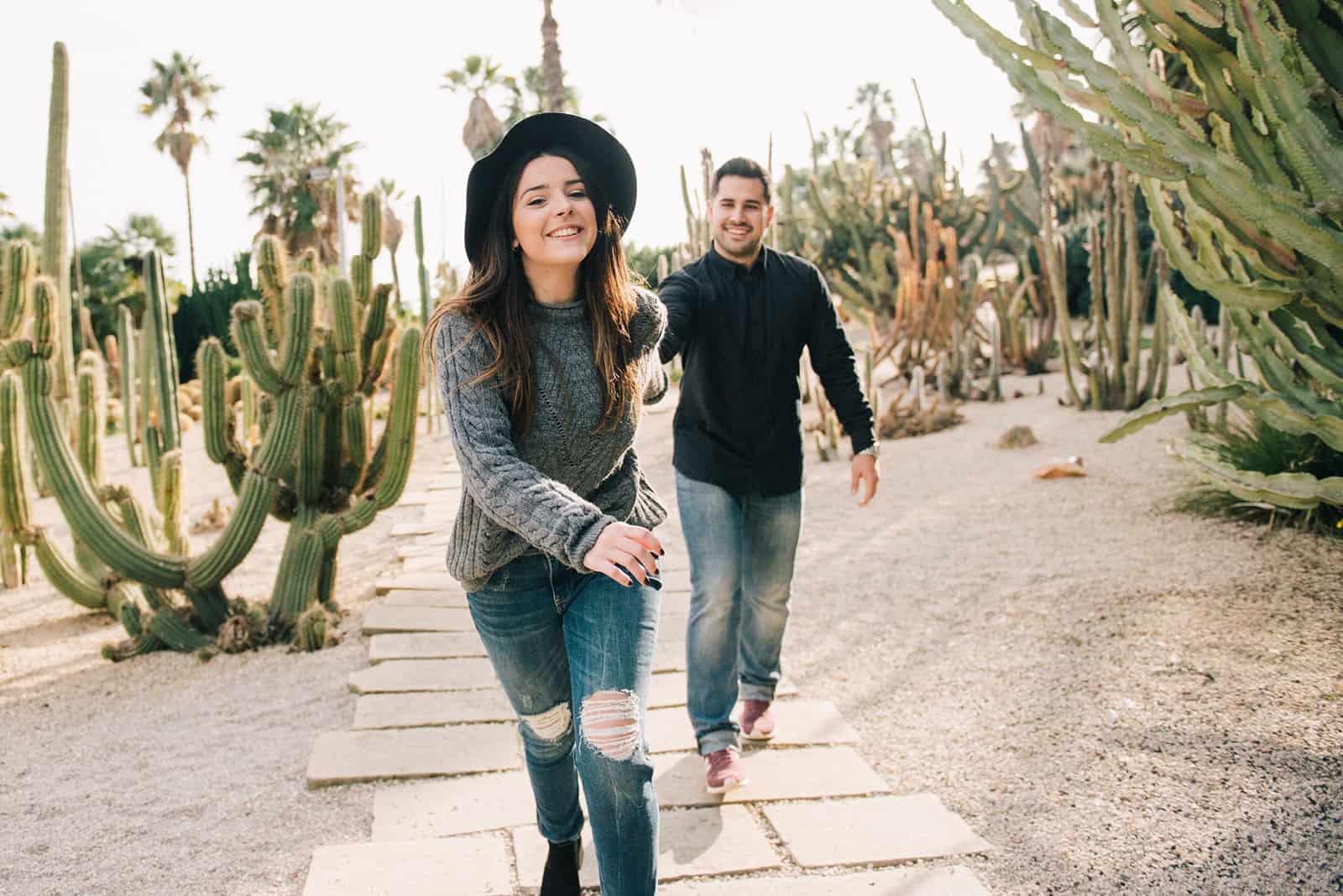 une femme tenant la main avec un homme et courir parmi les plantes de cactus