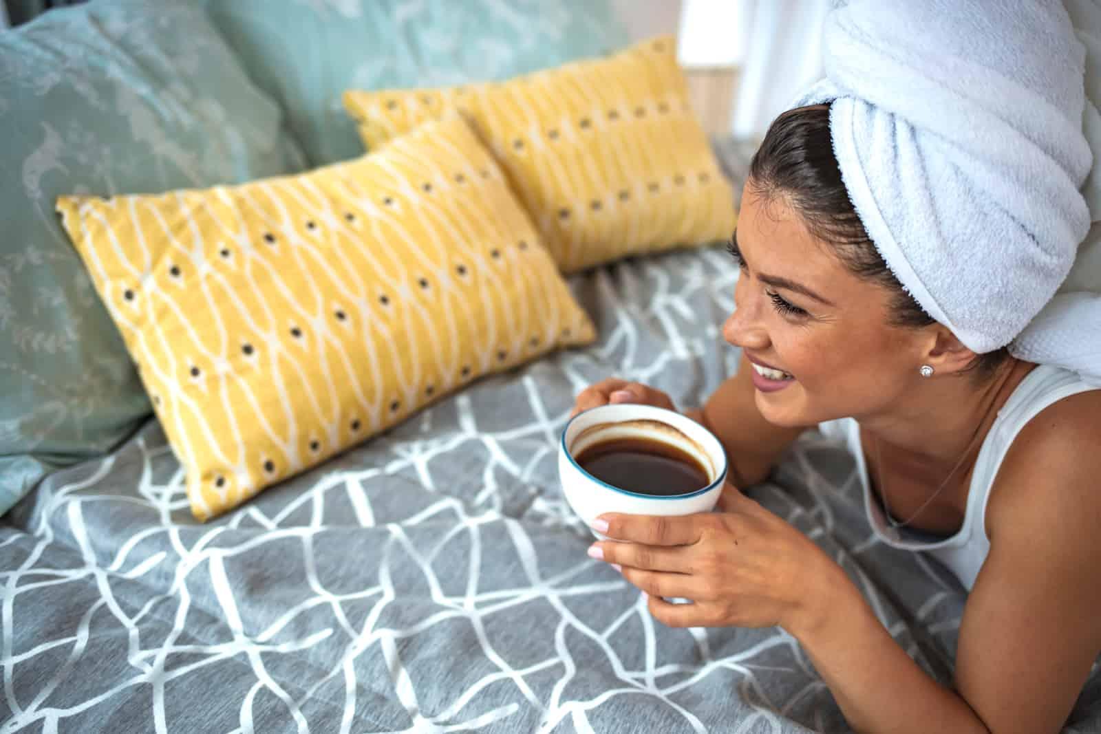 fille allongée sur un lit et buvant du café