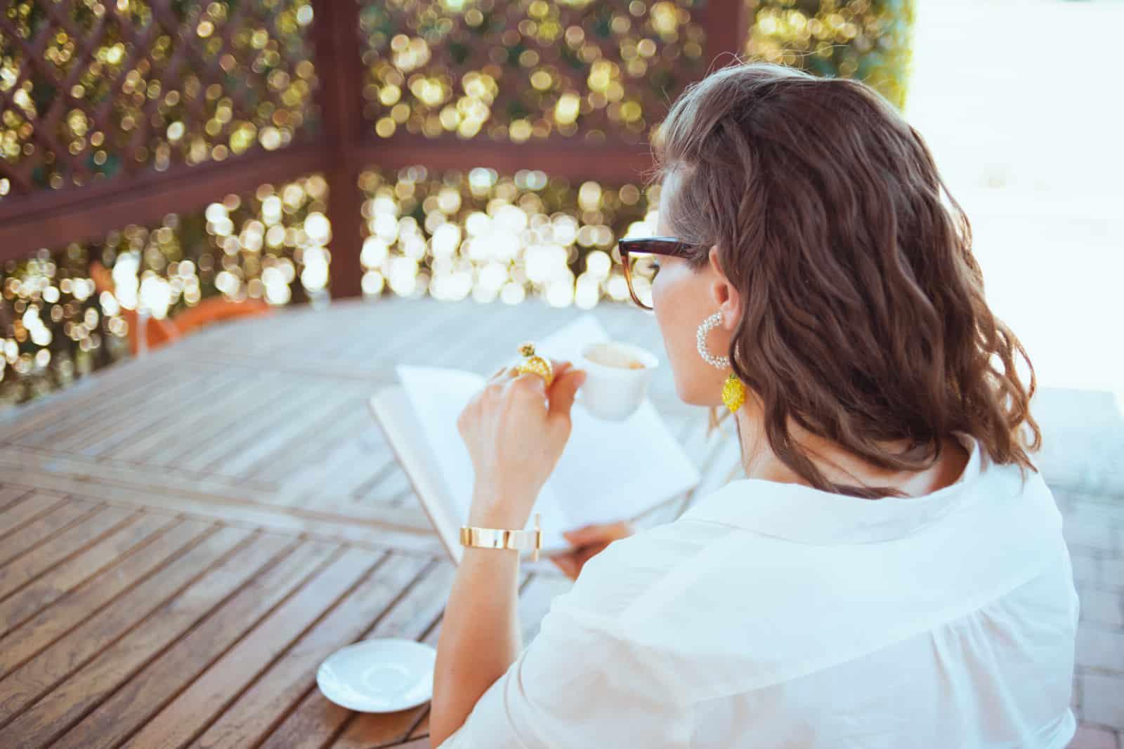 fille buvant du café et lisant un livre